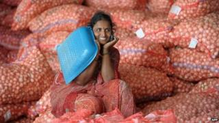 Indian labourers speaks on a cellular telephone as she sits on onion bags