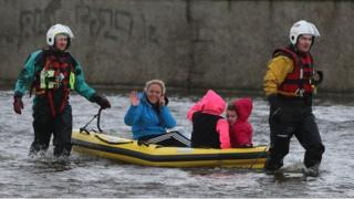 Residents use a boat to navigate flood waters after a flash flood on the Lee Estate in Limerick City