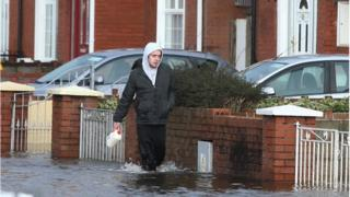 A man walks through flood waters after a flash flood on the Lee Estate in Limerick City