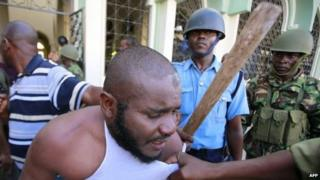"A Muslim man is detained by police officers at the Masjid Mussa Mosque in Kenya""s coastal town of Mombasa February 2, 2014."