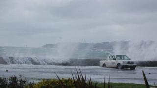 Waves crashing over wall onto car