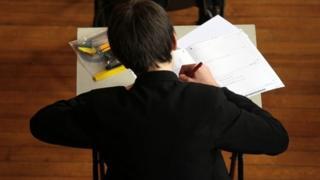 Boy writing in an exam
