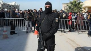 Tunisian Special Forces member stands outside the house which has militants inside.