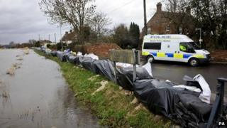 A police van parked behind temporary flood defences at a river bank