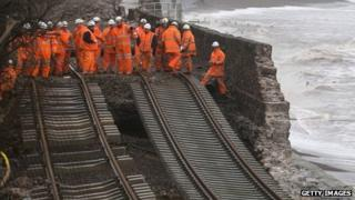 Engineers inspect a section of a mainline rail route swept away in Dawlish, Devon
