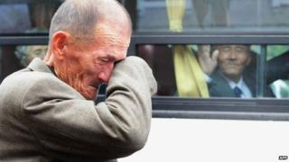 File photo: An elderly South Korean man wipes his tears as a North Korean relative [in the bus] waves to say good-bye after a luncheon during a separated family reunion meeting at the Mount Kumgang resort on the North's southeastern coast, 31 October 2010