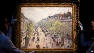 Sotheby's employees hold up Camille Pissarro's Le Boulevard Montmartre, matinee de printemps (1897)