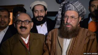 """Tehreek-e-Taliban Pakistan (TTP) committee member and senior religious party leader Maulana Sami-ul-Haq (R) shakes hands with Special Assistant to Pakistan""""s prime minister Irfan Siddiqui after their meeting at the Khyber Pakhtunkhwa House in Islamabad on February 6, 2014."""