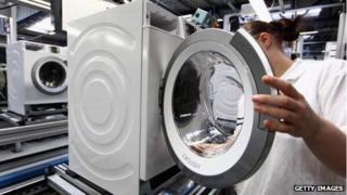 A factory worker assembles a washing machine