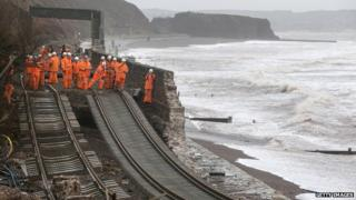 Railway workers inspect the main Exeter to Plymouth railway line that has been closed due to parts of it being washed away by the sea at Dawlish, Devon