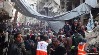 Crowds of Yarmouk camp residents wait to be allowed to join the queue for aid distribution
