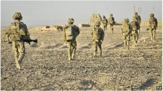 A line of soldiers walking through very dry terrain