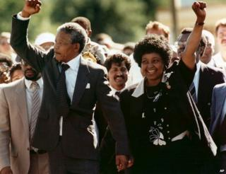 Nelson Mandela and his wife, Winnie, raise clenched fists as they walk hand-in-hand upon his release from prison