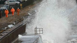 Railway workers are splashed by giant waves that crashed into the coast at Dawlish