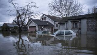 house and car under floodwater
