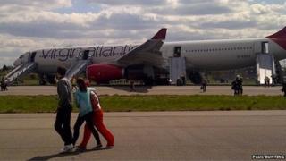 Passengers disembark the plane