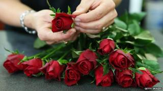 A florist prepares a bunch of roses