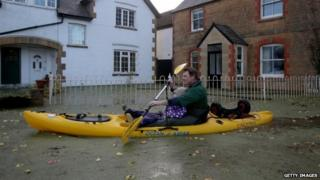 A resident uses a canoe on flood water past houses on the road leading to Muchelney