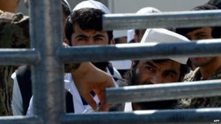Afghan detainees wait to be released during a ceremony to hand over Bagram prison to the Afghanistan government at Bagram Prison facilities on 25 March 2013.