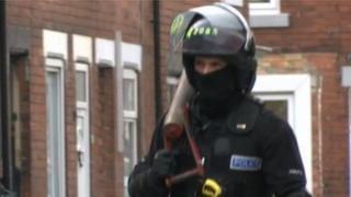 A police officer carries away a battering ram