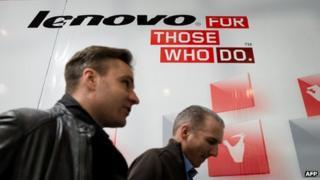 Two men walk by Lenovo billboard in Hong Kong