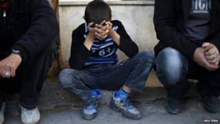 The son of Ibrahim Mansour holds his head in his hands outside the mortuary in Gaza City (13 February 2014)