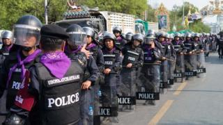 Police wait at the Rachadamnoen, Bangkok, on 14 February 2014
