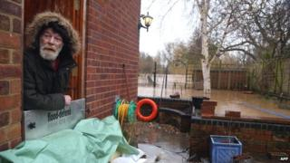 Resident Richard Perry looks out of the back door of his house protected by sang bags in Alney Island, Gloucester