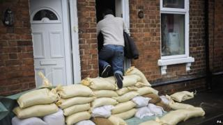 A local resident climbs over sandbags protecting houses on Alney Terrace, Gloucester.