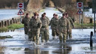 Members of The King's Royal Hussars wade through flood water on Chertsey Meads