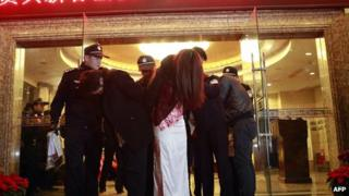 Chinese policemen arrest suspected prostitutes in Dongguan
