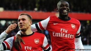 Lukas Podolski of Arsenal celebrates with team mate Yaya Sanogo
