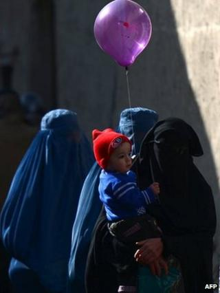 An Afghan burka-clad woman walks with her child holding a balloon in Kabul on 15 February 2014