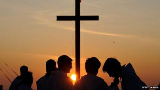 Priests stand by a crucifix with the sun setting behind