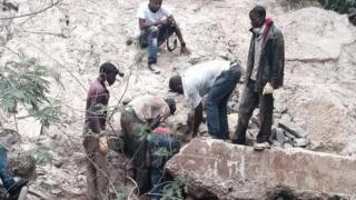 Illegal miners pulling out the body of a dead miner from a mine shaft in Benoni, South Africa