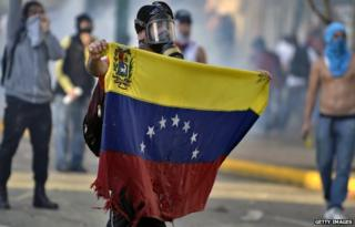 An anti-government protestor in Venezuela holding up a battered flag
