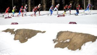 Cross-country skiers glide past a dry patch of melted snow during a race in Sochi on 15 February.