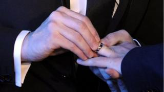 Men exchanging wedding rings in gay marriage ceremony