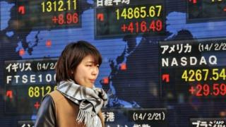 A woman passes before a share prices board in Tokyo on February 21, 2014