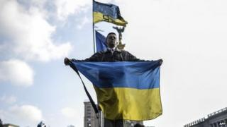 A man holds a Ukrainian flag as he stands on Kiev's Independence Square
