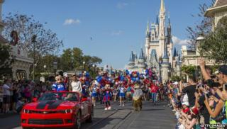 Magic Kingdom castle in background of confetti parade with Mickey Mouse