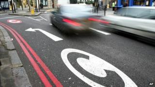 Cars drive pass congestion charge signs