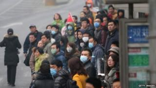 This picture taken on 24 February 2014 shows residents waiting for buses in a bus station in haze-covered Beijing