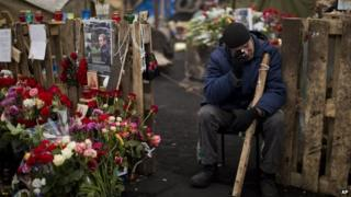 Man cries near a memorial for killed protesters at Kiev's Independence Square (25 February 2014)