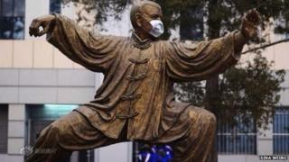 A statue with a face mask at Peking University