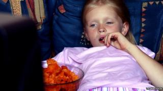 A girl eating in front of a television