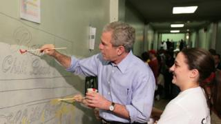 President George W Bush helps paint a mural in Washington DC in 2007