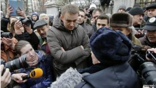 Alexei Navalny speaks to a police officer outside a courthouse in Moscow on 24 February