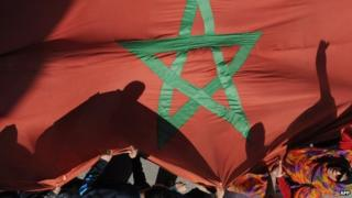 Moroccan protesters hold a giant national flag during a demonstration outside the French embassy in Rabat