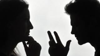 A silhouetted couple arguing